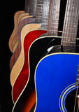 Acoustic guitars isolated on black background. A selection of blue, red, black and natural wood colored acoustic six string guitars isolated on a black Stock Images