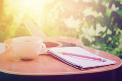Acoustic guitars with a notebook and cup of coffee on table,music relax time in garden. Acoustic guitars with a notebook and cup of coffee on table,music relax Stock Photos