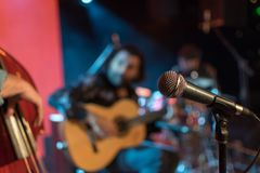 Acoustic trio band performing on a stage in a nightclub, with th. E microphone in focus waiting for its singer Royalty Free Stock Photography