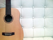 Acoustic On White Sofa. Acoustic Guitar On White Sofa Royalty Free Stock Images
