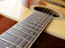 Acoustic wood guitar close up on wooden background with fretboard, strings, and tuners for music blogs, musician social media. Acoustic wood guitar close up on royalty free stock photos