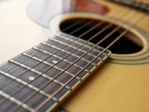 Acoustic wood guitar close up on wooden background with fretboard, strings, and tuners for music blogs, musician social media. Acoustic wood guitar close up on stock photography
