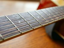 Acoustic wood guitar close up on wooden background with fretboard, strings, and tuners for music blogs, musician social media. Acoustic wood guitar close up on royalty free stock photo