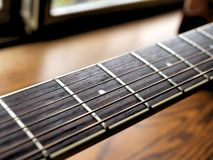 Acoustic wood guitar close up on wooden background with fretboard, strings, and tuners for music blogs, musician social media. Acoustic wood guitar close up on royalty free stock photography