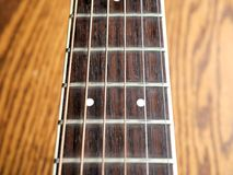 Acoustic wood guitar close up on wooden background with fretboard, strings, and tuners for music blogs, musician social media. Acoustic wood guitar close up on royalty free stock images