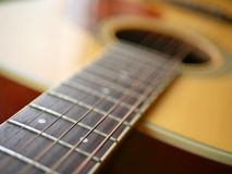 Acoustic wood guitar close up on wooden background with fretboard, strings, and tuners for music blogs, musician social media. Acoustic wood guitar close up on stock image