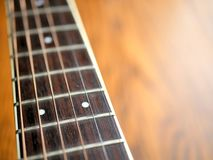 Acoustic wood guitar close up on wooden background with fretboard, strings, and tuners for music blogs, musician social media. Acoustic wood guitar close up on stock photos