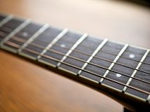 Acoustic wood guitar close up on wooden background with fretboard, strings, and tuners for music blogs, website banners. Acoustic wood guitar close up on wooden stock images