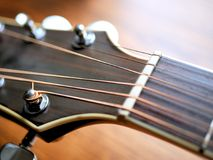 Acoustic wood guitar close up on wooden background with fretboard, strings, and tuners for music blogs, website banners. Acoustic wood guitar close up on wooden royalty free stock images