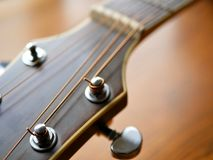Acoustic wood guitar close up on wooden background with fretboard, strings, and tuners for music blogs, website banners. Acoustic wood guitar close up on wooden stock photography