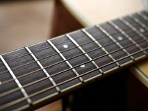 Acoustic wood guitar close up on wooden background with fretboard, strings, and tuners for music blogs, website banners. Acoustic wood guitar close up on wooden royalty free stock photos