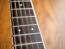 Acoustic wood guitar close up on wooden background with fretboard, strings, and tuners for music blogs, website banners. Acoustic wood guitar close up on wooden royalty free stock photo