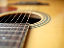Acoustic wood guitar close up on wooden background with fretboard, strings, and tuners for music blogs, website banners. Acoustic wood guitar close up on wooden royalty free stock photography