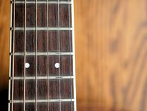 Acoustic wood guitar close up on wooden background with fretboard, strings, and tuners for music blogs, website banners. Acoustic wood guitar close up on wooden stock photo