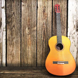 Acoustic wooden guitar leaning on a wooden fence. stock photos