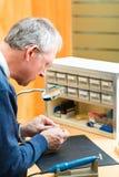 Acoustician работая на аппарате для тугоухих Стоковые Изображения