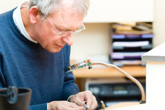 Acoustician working on a hearing aid. Hearing aid acoustician at work, he is working on a hearing aid for hearing impaired persons Royalty Free Stock Image