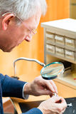 Acoustician working on a hearing aid. Hearing aid acoustician at work, he is working on a hearing aid for hearing impaired persons Royalty Free Stock Images