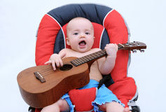 Acoustics. Beautiful litle baby playing guitar stock images