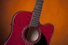 Acoustique rouge de guitare d'isolement sur l'or Photographie stock