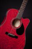 Acoustique rouge de guitare d'isolement sur le noir Image libre de droits