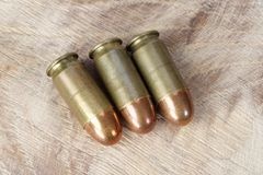 .45 ACP Automatic Colt Pistol, or .45 Auto 11.43x23mm a handgun cartridges designed by John Browning in 1905. On wooden background stock image