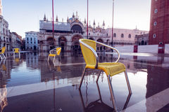 Acqua Alta In Venice. Chairs standing in water in st mark`s square Stock Image