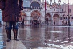 Acqua Alta In Venice. Woman in rubber boots walking over st mark`s square in venice Stock Images