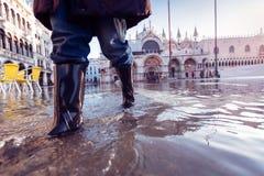 Acqua Alta In Venice. Woman in rubber boots walking over st mark`s square in venice Stock Photo