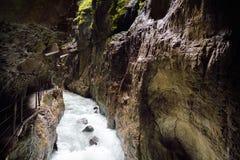 Acqua blu che entra nella gola o nel Partnachklamm di Partnach, inciso tramite una torrente montano nella valle di Reintal vicino immagini stock
