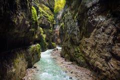 Acqua blu che entra nella gola o nel Partnachklamm di Partnach, inciso tramite una torrente montano nella valle di Reintal vicino immagine stock libera da diritti