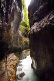 Acqua blu che entra nella gola o nel Partnachklamm di Partnach, inciso tramite una torrente montano nella valle di Reintal vicino Fotografie Stock Libere da Diritti