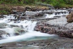 Acqua blu del fiume della montagna che scorre dal picco, esposizione lunga Immagine Stock