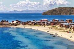 Acqua blu e costa del lago Titicaca, barche, gente di camminata e Fotografia Stock
