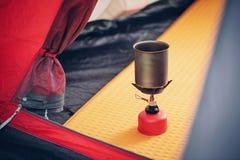 Acqua bollente in bollitore sulla stufa di campeggio portatile Fotografie Stock
