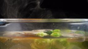 Acqua bollente con vapore, cucinante le verdure in pentola di vetro video d archivio