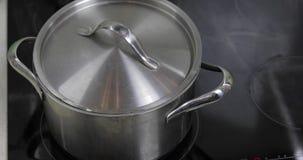 Acqua bollente nella pentola che ? coperta di coperchio nella cucina stock footage