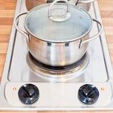 Acqua bollente in vaso del metallo sulla piastra riscaldante Fotografie Stock Libere da Diritti