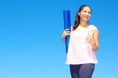 Acqua in bottiglia della tenuta della donna della corsa mista e stuoia di yoga Fotografia Stock Libera da Diritti