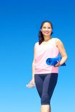 Acqua in bottiglia della tenuta della donna della corsa mista e stuoia di yoga Fotografia Stock
