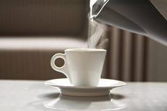 Acqua calda che entra da una teiera in una tazza bianca Immagini Stock Libere da Diritti