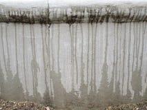Acqua che gocciola giù una parete grigia immagini stock