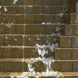 Acqua che precipita a cascata giù sui mattoni fotografie stock
