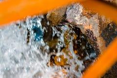 Acqua che precipita sopra le rocce sparate fra le stecche del ponte fotografia stock libera da diritti