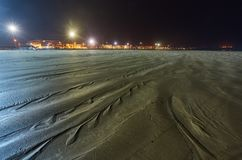 Acqua che retrocede alla bassa marea con le linee strutturate nella sabbia e che perfino luce solare che riflette lungo i bordi fotografia stock