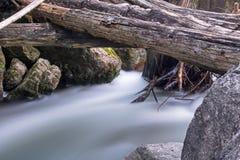 Acqua che scorre sotto il ponte di ceppo Fotografia Stock Libera da Diritti