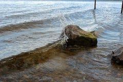 Acqua che spruzza su una roccia Fotografie Stock