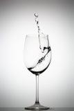 Acqua che spruzza in un vetro di vino Immagine Stock