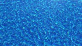 Acqua chiara d'ondeggiamento nella piscina con il fondo blu, vista superiore archivi video