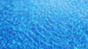 Acqua chiara d'ondeggiamento nella piscina con il fondo blu, vista superiore video d archivio